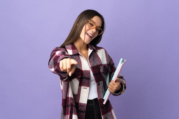 Młoda studentka kobieta na białym tle na fioletowy wskazując przód z szczęśliwym wyrazem