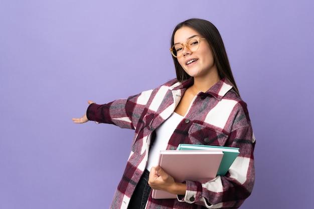 Młoda studentka kobieta na białym tle na fioletowym wyciągając ręce na bok za zaproszenie do przyjścia