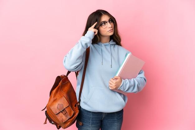 Młoda studentka kobieta na różowym tle, mając wątpliwości i myślenie