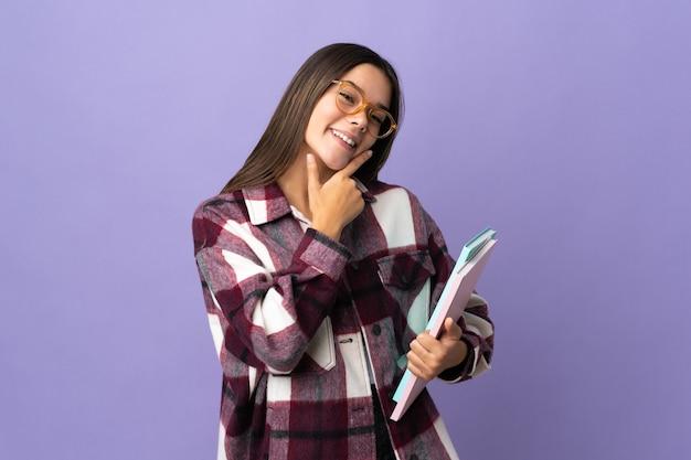 Młoda studentka kobieta odizolowywająca na fioletowym szczęśliwa i uśmiechnięta