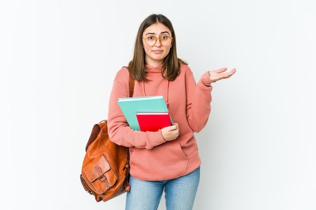 Młoda studentka kobieta wątpi i wzrusza ramionami w pytającym geście na białym tle na białej ścianie