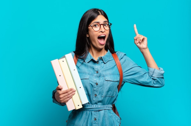 Młoda studentka latynoska czuje się jak szczęśliwy i podekscytowany geniusz po zrealizowaniu pomysłu, radośnie podnosząc palec, eureka!