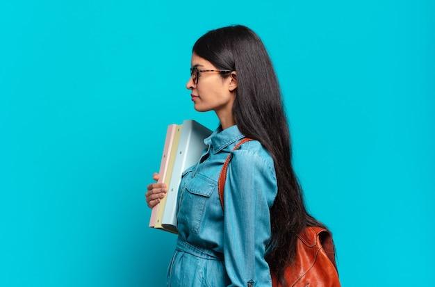 Młoda studentka latynoska w widoku profilu, chcąca skopiować przestrzeń do przodu, myśląca, wyobrażająca sobie lub marząca