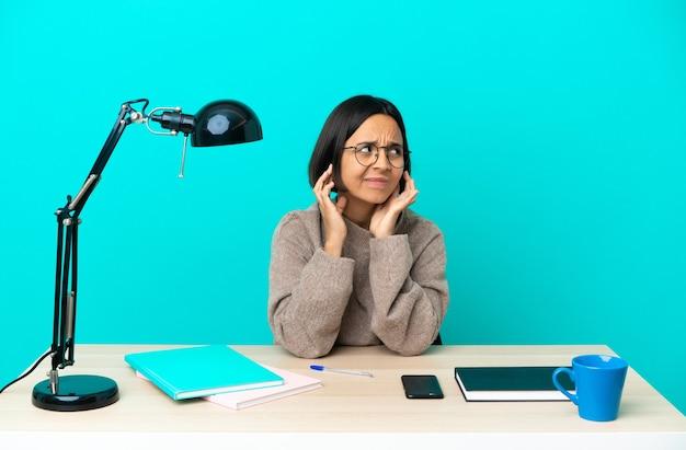 Młoda studentka mieszanej rasy kobieta studiująca na stole sfrustrowana i zakrywająca uszy