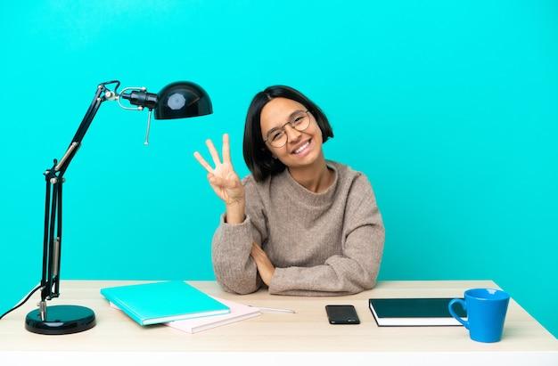 Młoda studentka mieszanej rasy kobieta studiująca na stole szczęśliwa i licząca trzy palcami