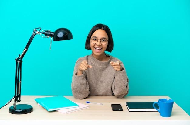 Młoda studentka mieszanej rasy kobieta studiująca na stole zaskoczona i wskazująca przód