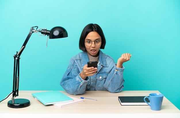Młoda studentka mieszanej rasy kobieta studiująca na stole zaskoczona i wysyłająca wiadomość