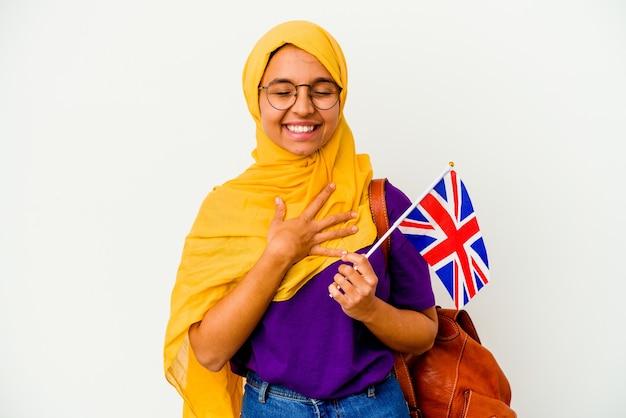 Młoda studentka muzułmanka na białym tle śmieje się głośno trzymając rękę na klatce piersiowej.