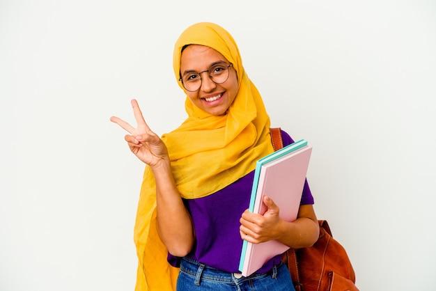 Młoda studentka muzułmańska kobieta ubrana w hidżab na białym radosna i beztroska pokazująca palcami symbol pokoju.