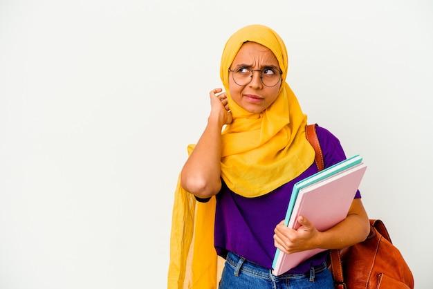 Młoda studentka muzułmańska kobieta ubrana w hidżab na białym tle na białej ścianie dotykając tyłu głowy, myśląc i dokonując wyboru.