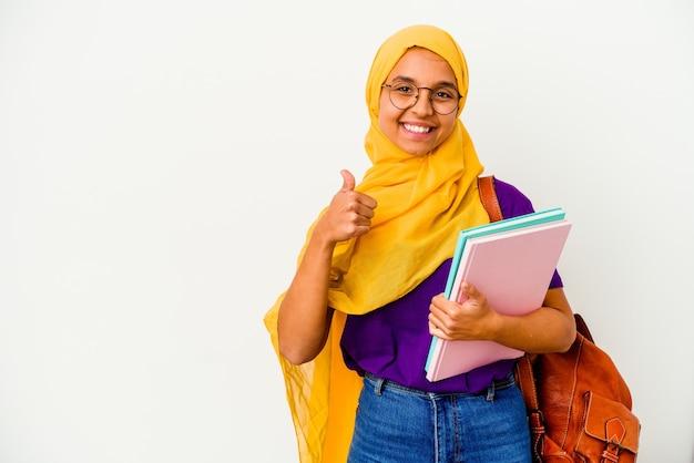 Młoda studentka muzułmańska kobieta ubrana w hidżab na białym tle na białej ścianie uśmiechnięta i podnosząca kciuk do góry