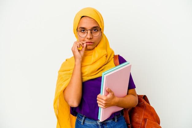 Młoda studentka muzułmańska kobieta ubrana w hidżab na białym tle na białej ścianie z palcami na ustach, zachowując tajemnicę.