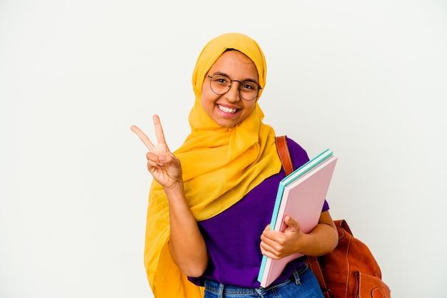 Młoda studentka muzułmańska kobieta ubrana w hidżab na białym tle pokazując numer dwa palcami.