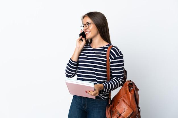 Młoda studentka na białym tle trzymająca kawę na wynos i telefon komórkowy