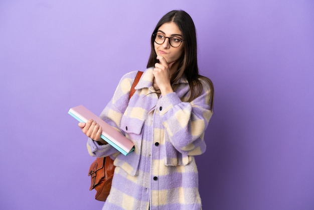 Młoda studentka na fioletowym tle, mająca wątpliwości i myśląca