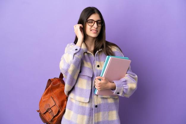 Młoda studentka na fioletowym tle sfrustrowana i zakrywająca uszy