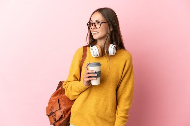 Młoda studentka na odosobnionym różowym tle, patrząc w bok i uśmiechnięta