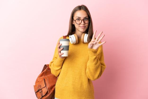 Młoda studentka na odosobnionym różowym tle szczęśliwa i licząca cztery palcami