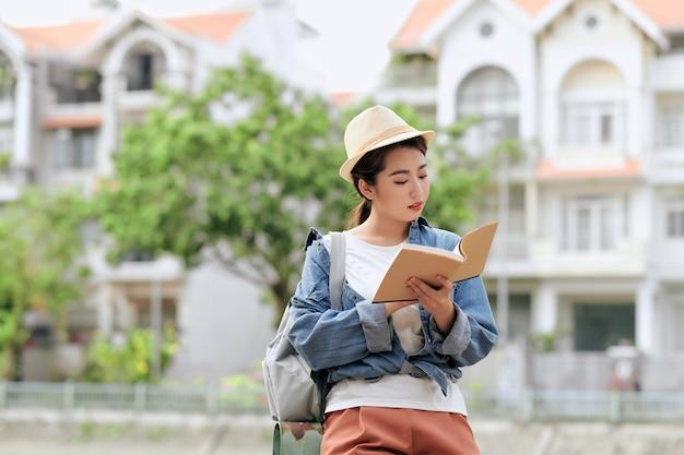 Młoda studentka na ulicy z plecakiem i książkami