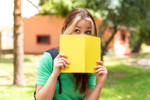 Młoda studentka na zewnątrz trzymająca notatnik