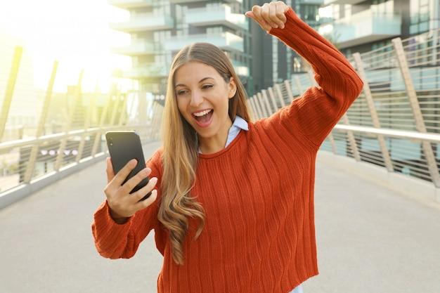 Młoda studentka obchodzi dobre wieści na jej telefon komórkowy doping