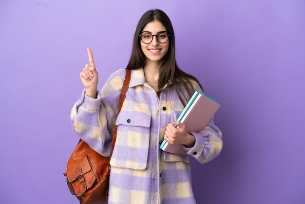 Młoda studentka odizolowana na fioletowym tle wskazująca świetny pomysł