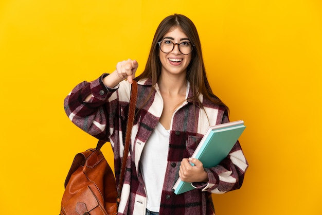 Młoda studentka odizolowana na żółtym tle zaskoczona i wskazująca przód