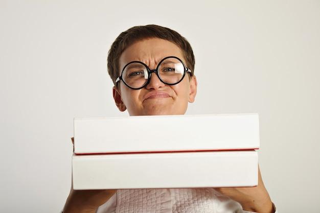 Młoda studentka okazuje emocjonalny wyraz i rozczarowanie z powodu rozpoczęcia nowej pracy papierkowej w teczkach z dokumentami, które trzyma przed sobą