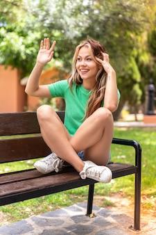 Młoda studentka pozdrawiająca na zewnątrz