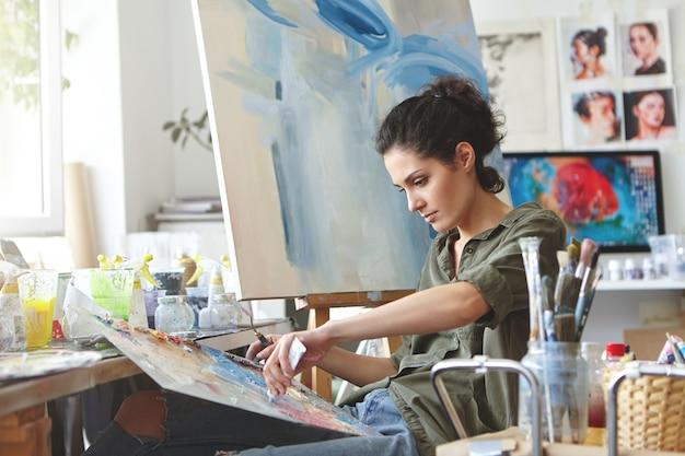 Młoda studentka prowadząca zajęcia w pracowni artystycznej, ucząca się rysować krajobrazy, próbująca mieszać różne akwarele na tekturze. skoncentrowana kobieta o ciemnych włosach, ubrana swobodnie, maluje