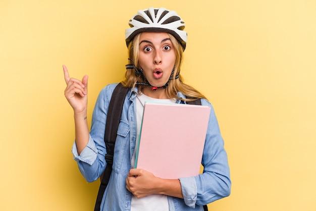 Młoda studentka rasy kaukaskiej nosi kask rowerowy na białym tle na żółtym tle, wskazując na bok