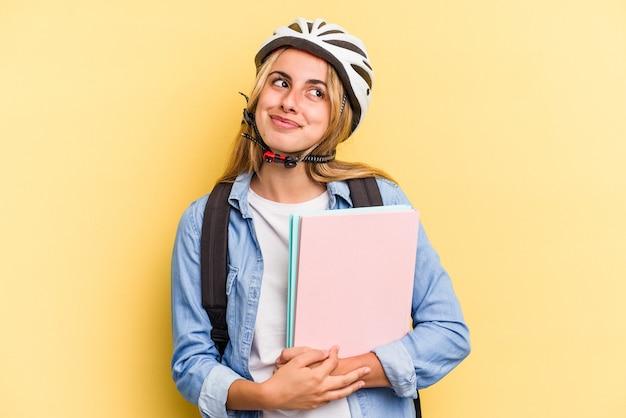 Młoda studentka rasy kaukaskiej nosząca kask rowerowy na białym tle na żółtym tle marząca o osiągnięciu celów i celów