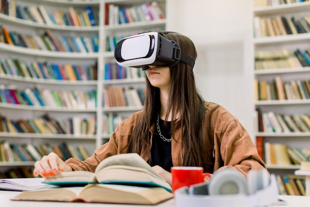 Młoda studentka rasy kaukaskiej w brązowej koszuli siedzi przy stole z książkami w bibliotece uczelni i studiuje za pomocą gogli vr