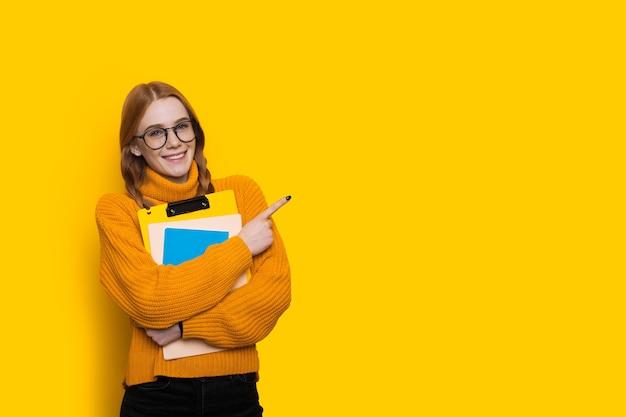 Młoda studentka rasy kaukaskiej z rudymi włosami i piegami w okularach i trzymająca foldery wskazuje na żółtą wolną przestrzeń obok niej
