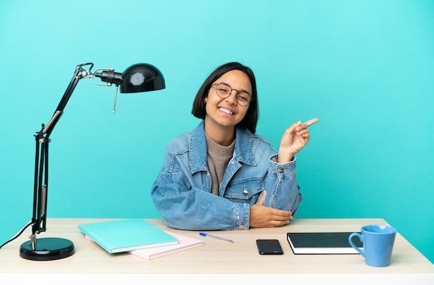 Młoda studentka rasy mieszanej kobieta studiująca na stole wskazującym palcem w bok