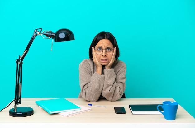 Młoda studentka rasy mieszanej kobieta studiująca na stole, wykonująca nerwowy gest
