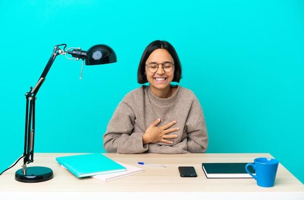 Młoda studentka rasy mieszanej, która studiuje na stole, często się uśmiecha