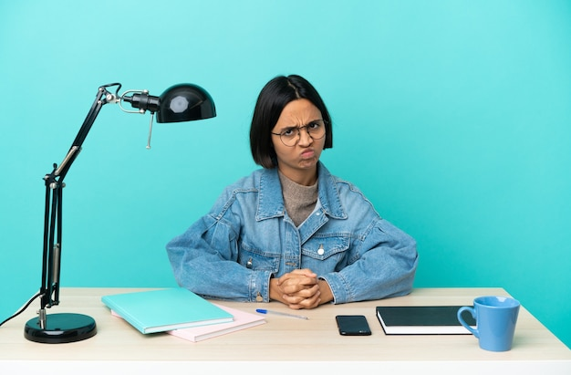 Młoda studentka rasy mieszanej, która studiuje na stole, czuje się zdenerwowana