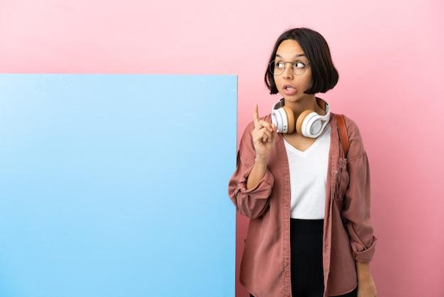Młoda studentka rasy mieszanej z dużym banerem na białym tle, myśląca o pomyśle wskazującym palec w górę