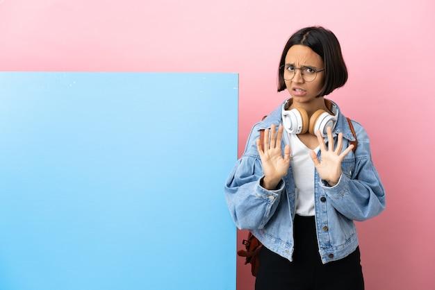 Młoda studentka rasy mieszanej z dużym banerem na białym tle nerwowe rozciąganie rąk do przodu