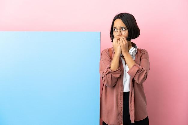 Młoda studentka rasy mieszanej z dużym banerem na białym tle zdenerwowana i przestraszona, przykładająca ręce do ust