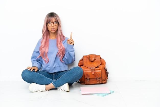 Młoda studentka rasy mieszanej z różowymi włosami siedząca na podłodze na białym tle skierowana w górę i zaskoczona