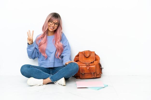 Młoda studentka rasy mieszanej z różowymi włosami siedząca na podłodze na białym tle szczęśliwa i licząca trzy palcami