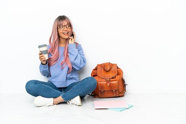 Młoda studentka rasy mieszanej z różowymi włosami, siedząca na podłodze na białym tle, trzymająca kawę na wynos i telefon komórkowy