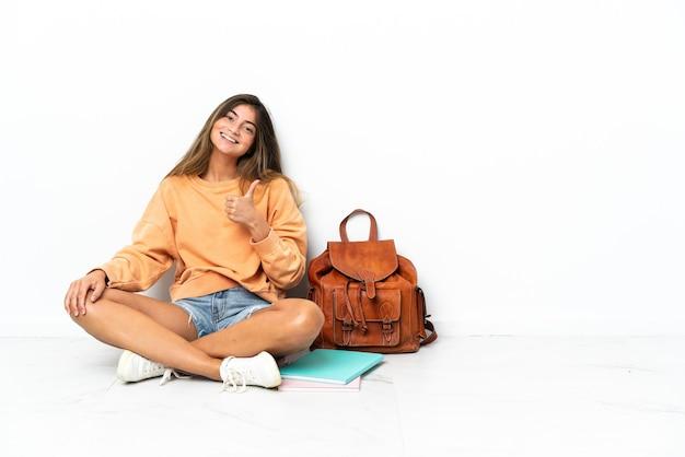 Młoda studentka siedząca na podłodze z laptopem na białym tle, pokazująca gest kciuka w górę