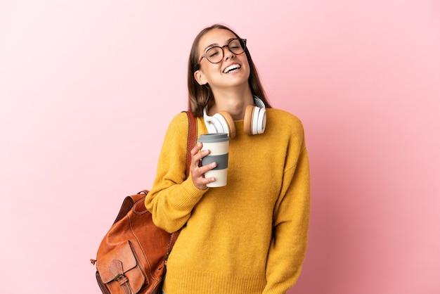 Młoda studentka śmiejąca się na odosobnionym różowym tle