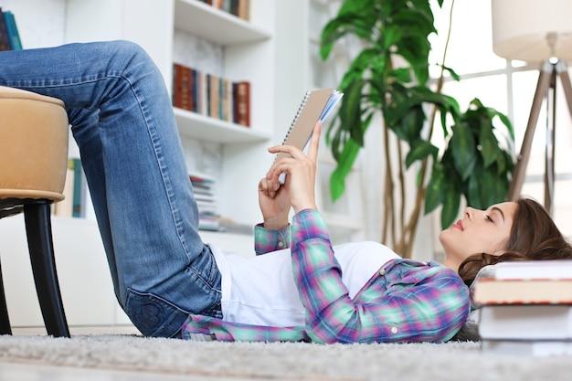 Młoda studentka studiująca w domu, przygotowująca się do egzaminów uniwersyteckich, leżąca na podłodze przy przytulnym domowym wnętrzu, otoczona stosem książek.