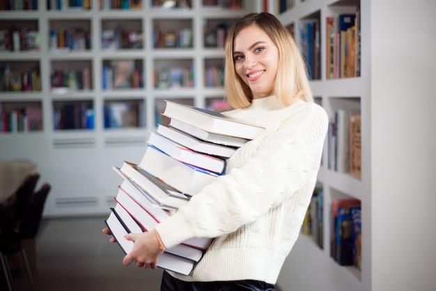 Młoda studentka studiuje w szkolnej bibliotece z wieloma książkami w ręku.