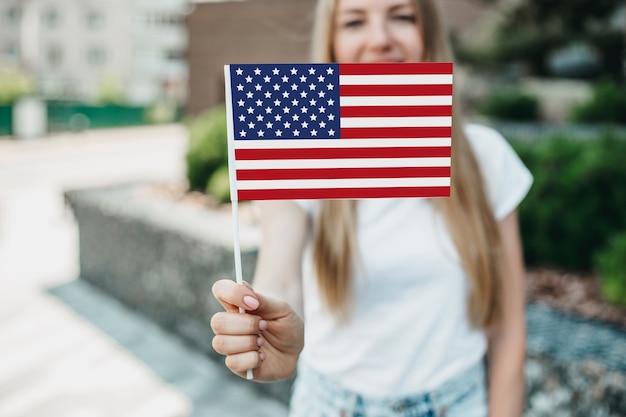 Młoda studentka uśmiecha się i pokazuje małą amerykańską flagę i stoi na tle uniwersytetu. ścieśniać