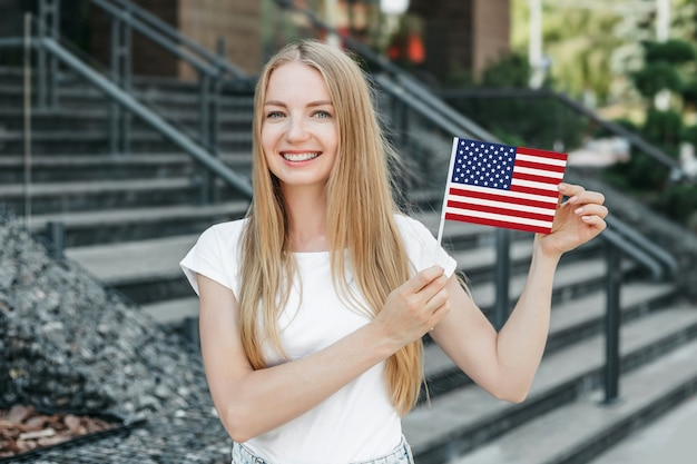 Młoda studentka uśmiecha się i pokazuje małą amerykańską flagę i stoi na tle uniwersytetu